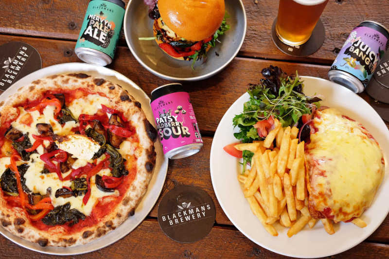 Cans of Blackman's Brewery beer and pub food.