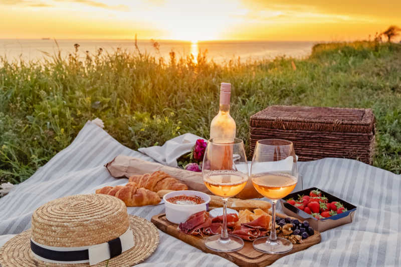Best boho picnic rugs Australia with food, wine, a hat, and sunset view.