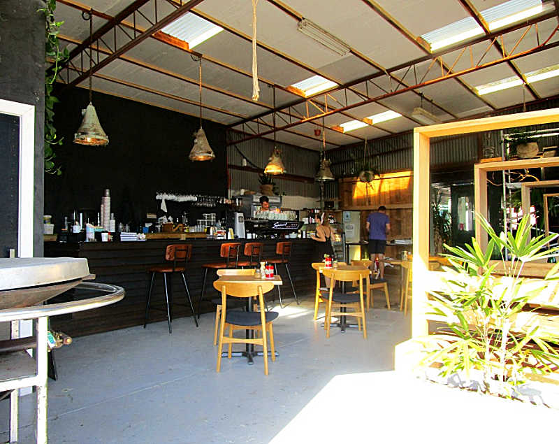 Box Office Cafe in Pakington Street entrance with tables and chairs and greenery.