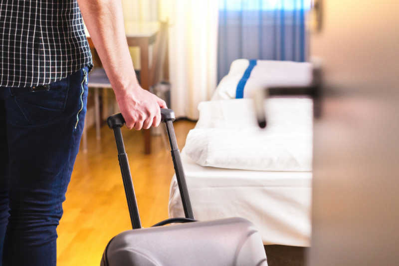 Person with suitcase entering cheap accommodation in Geelong.