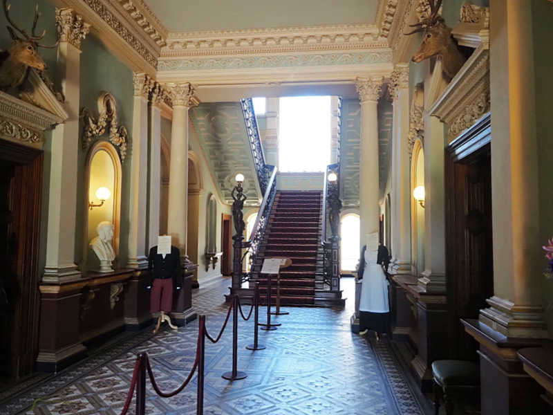 Chirnside Mansion Werribee entrance hall with stairway and mannequins in original attire.