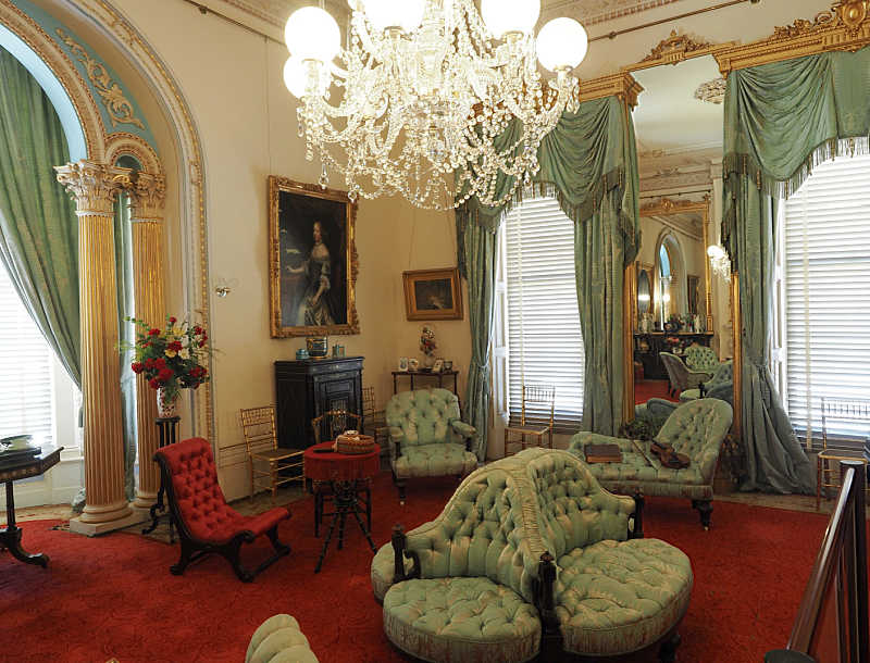 Image of the drawing room at Werribee Park Mansion with chandelier and upholstered chairs.