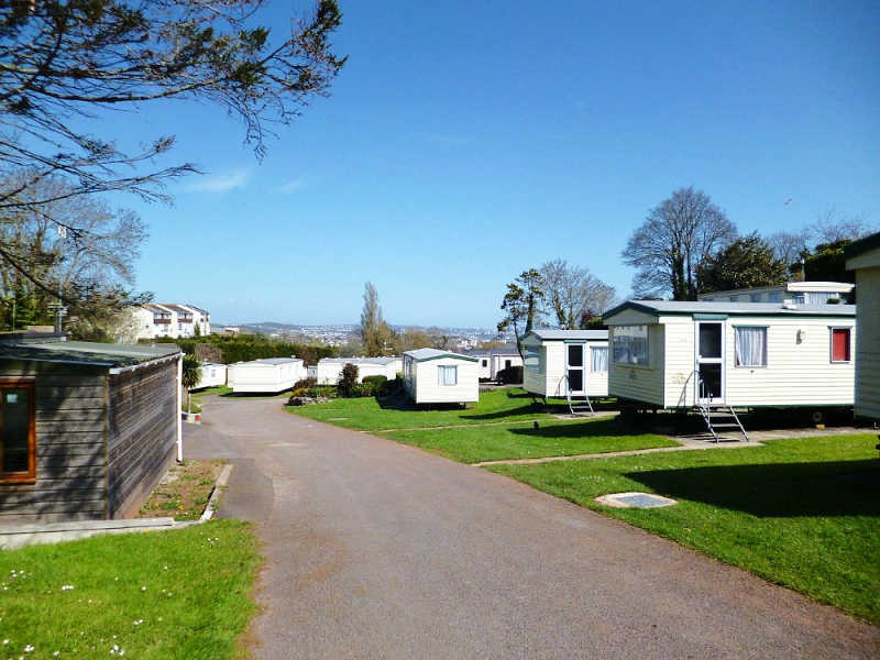 Image of holiday cabins, lush green grass, and a road at Geelong caravan parks