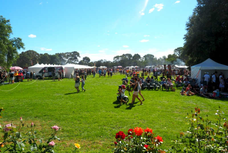 People strolling the lush lawns at the Lara Food and Wine Festival with roses in the foreground.