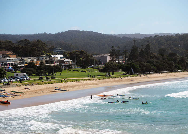 View of top accommodation Lorne, beach and kayaks with the Otway Ranges in the background.