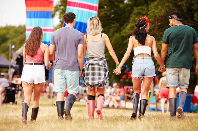 Group of friends walking and holding hands at Meredith Music Festival.