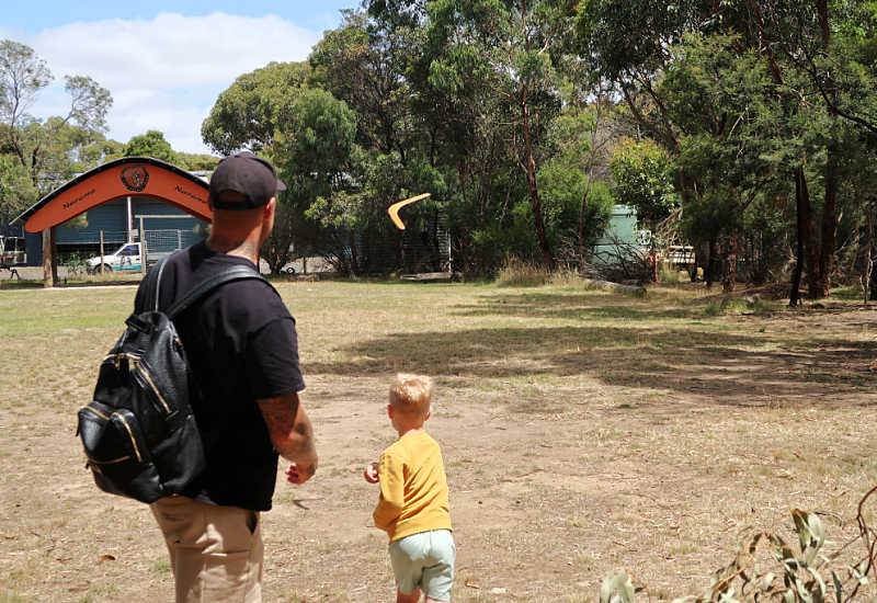Man with a small boy throwing a boomerang