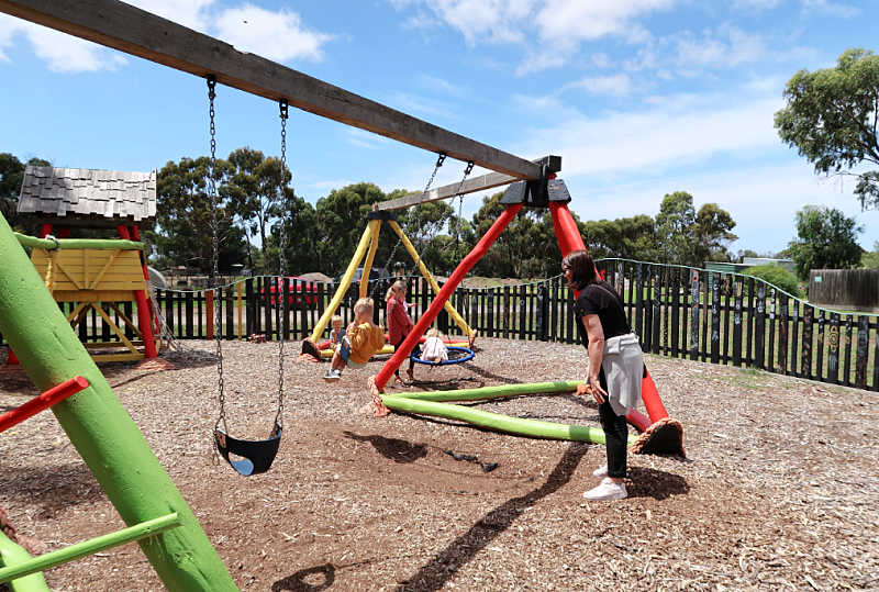 Small boy being pushed on the swings at the Narana Geelong playground.