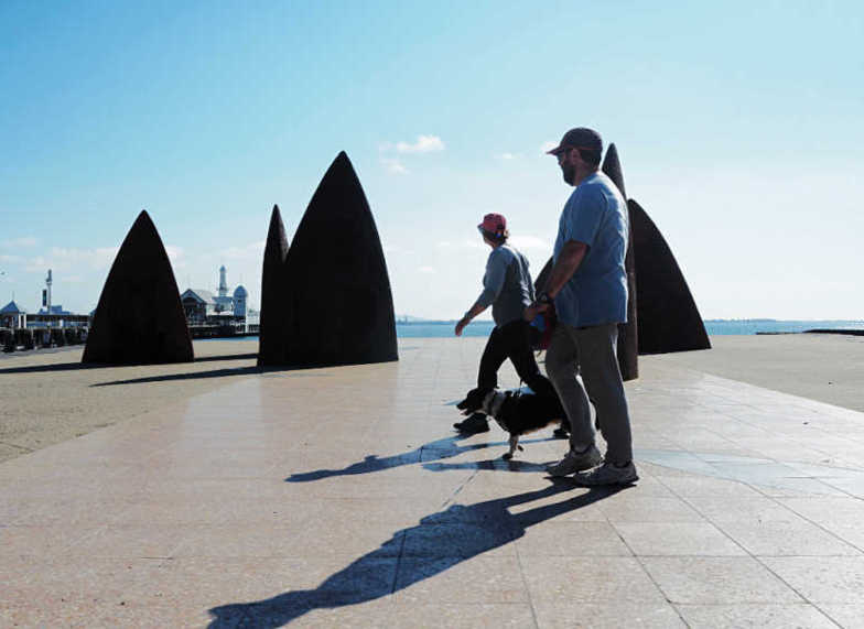 "Couple with dog walking past the Geelong public artwork sculpture ""North"" with Cunningham Pier in the background."