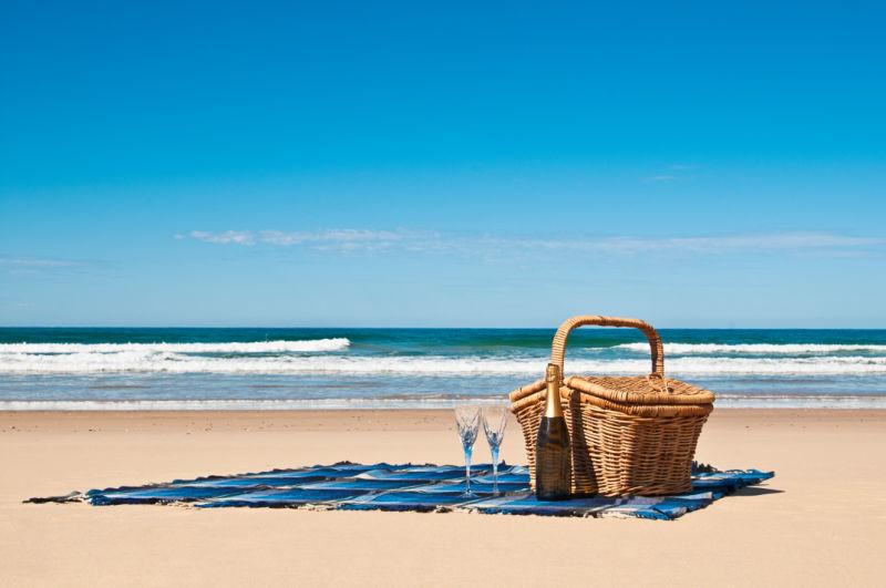 Best picnic baskets Australia beach, blanket and chapagne glasses.