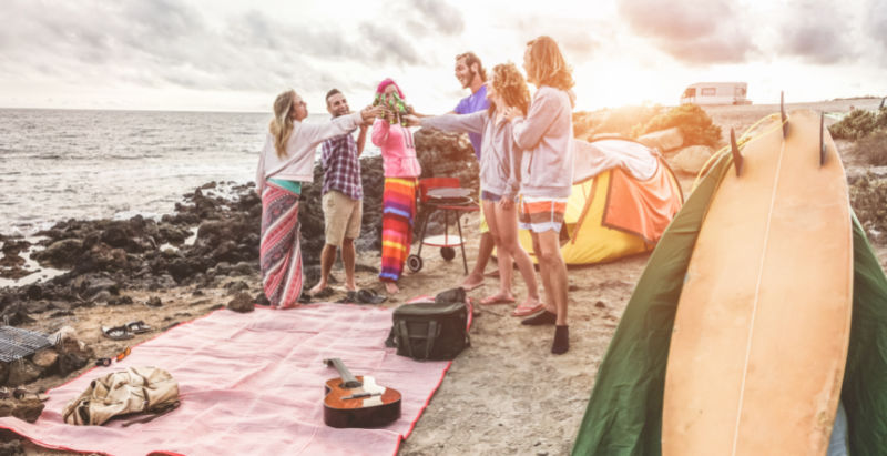 People celebrating next to a picnic rug at the beach in Australia.