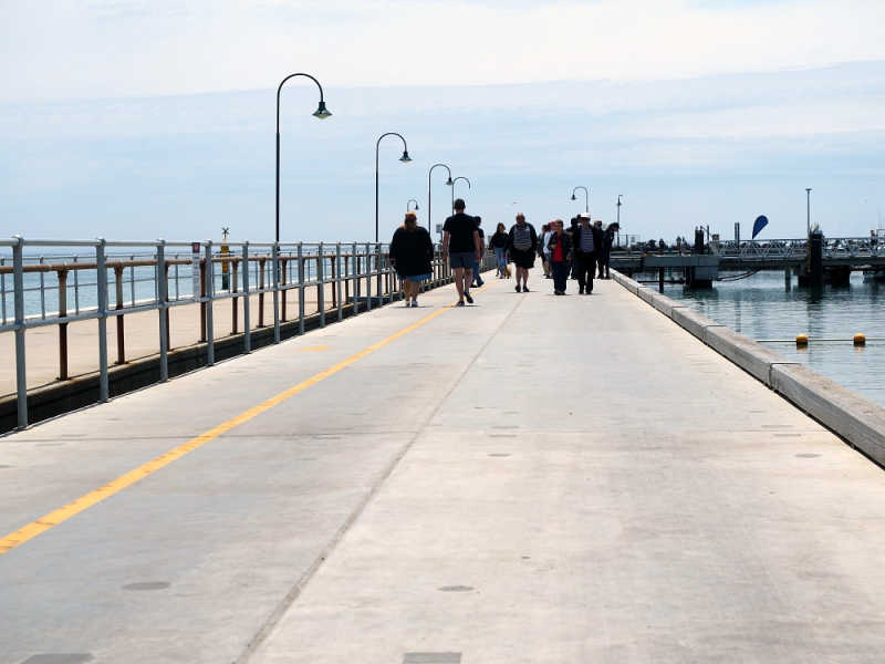 People walking on the Portarlington pier.