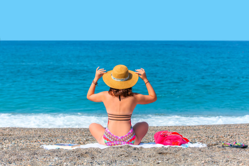 Woman at the beach sitting on a sand free towel in Australia.