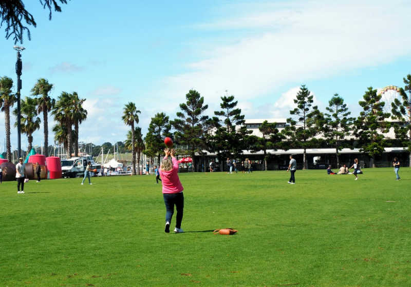 Woman catching a football at Steampacket Gardens Geelong.