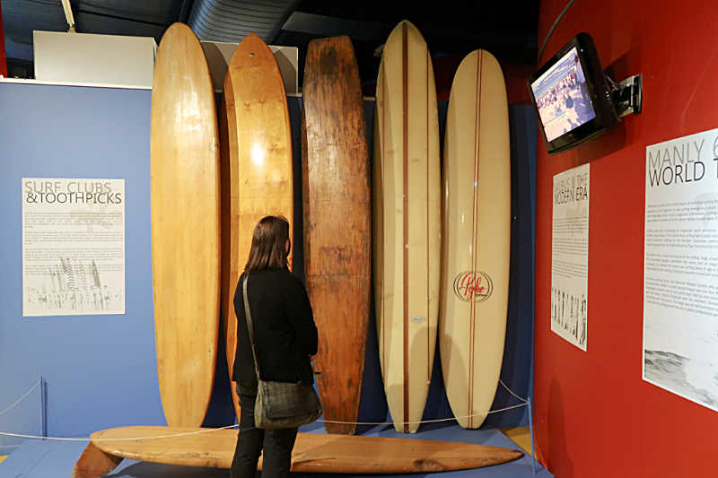 Woman looking at old surfboards at the Surfworld Museum Torquay
