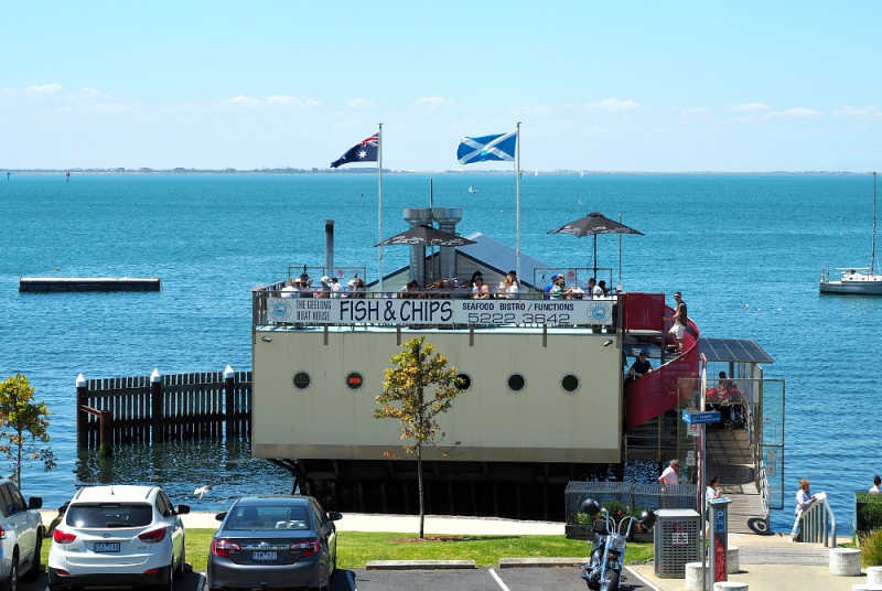 Photo of The Geelong Boat House with flags flying and Corio Bay in the background.