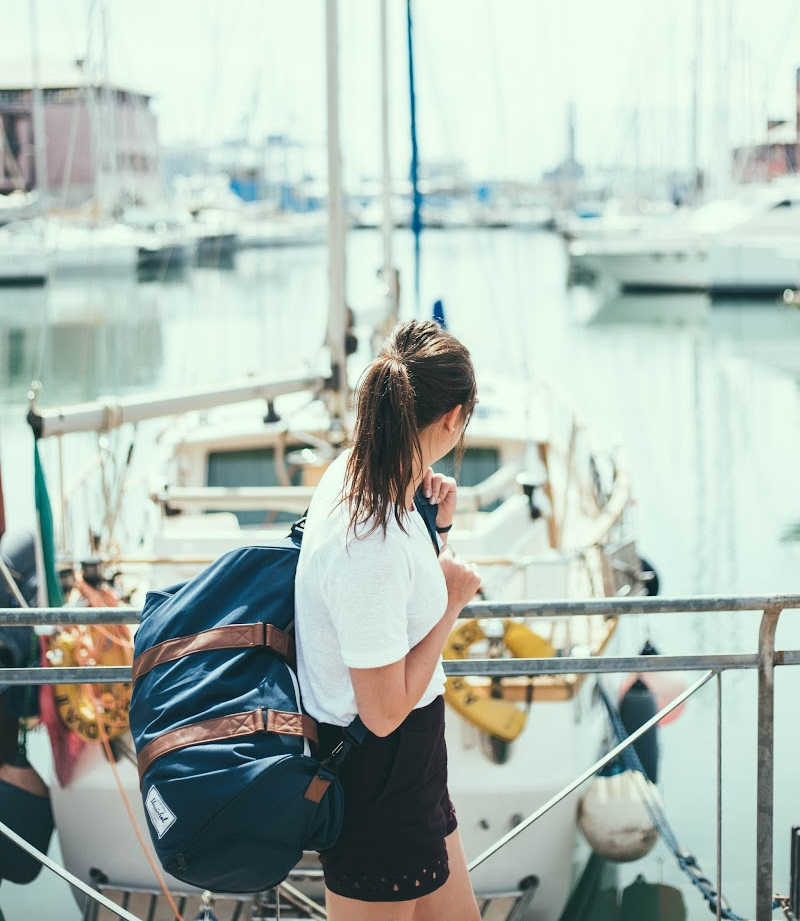 Young woman carrying a travel duffel on a jetty with boats