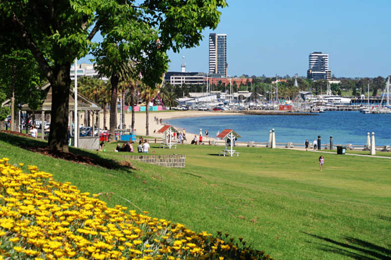 People picnicking on the lush Geelong Waterfront lawns with the bay and city skyline.
