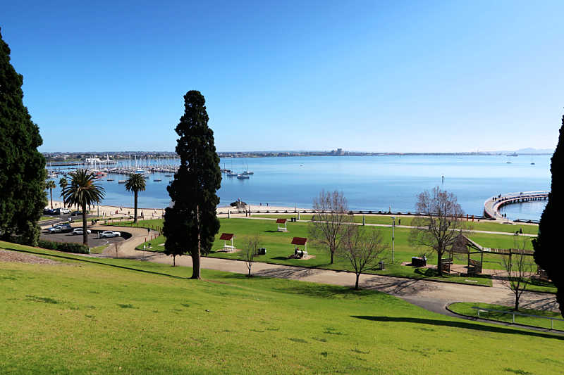 View of Waterfront Geelong with blue Corio Bay, green grass, boats, and trees.